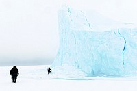 Inuit hunter collecting ice for water from in sea ice frozen iceberg, floe edge, Baffin bay, Nunavut, Canada.