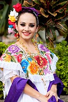 Young hispanic woman smiling while wearing Mexican folklore outfit.