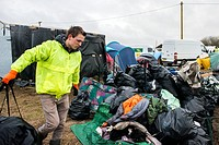 Calais, France. Volunteer worker cleaning up the assembled garbage, in The Jungle, a camp for illegal migrtants, bound for the UK.