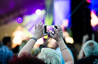 People using their mobile phones to record the band paying at The Big Tribute Music festival, Aberystwyth, August Bank Holiday weekend, Summer 2015.