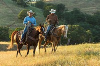 Two wranglers (cowboys) on horses, California, USA