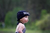 A female toddler in a swimming suit at Fish Lake, Spokane, Washington, USA.