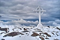 The summit cross on the snow covered summit of Galtymore, Galtee Mountains, County Tipperary, Ireland.