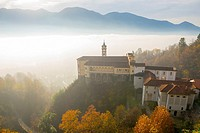 Monastery Madonna del Sasso with sea of fog and sunlight and swiss alps in Locarno, Switzerland.