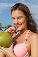 Woman (23 years old) on the beach with a coconut