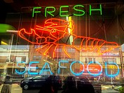 New York City, USA. Neon sign inside the window to a fresh seafood and fish store, Roosevelt Av, Queens.