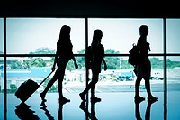 Silhouette of 3 female travelers at airport terminal.