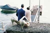 Wedding shoes and wedding couple on pier