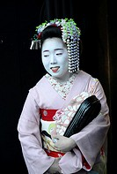 Portrait of an apprentice geisha (maiko) with white face, make-up, traditional kimono and hairstyle in Gion,Kyoto, Japan.