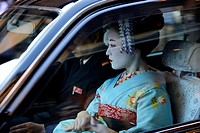 A geisha in a car in Gion district, Kyoto, Japan.