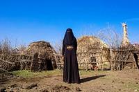 Ethiopia, Amhara Region, Artuma, an ethiopian oromo woman dressed in black burqa stands in front of her hut.