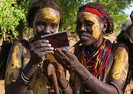 Ethiopia, Omo Valley, Omorate, dassanech tribe women looking polaroid pictures of themselves.