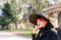 A pretty 23 year old red headed woman wearing a black straw hat looking away from the camera, outdoors.