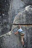 A woman climbing a rock at Yosemite National Park, California, USA