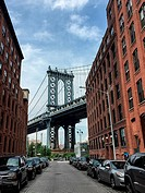 Manhattan Bridge, seen from the streets of the Dumbo neighborhood of Brooklyn, NY. Empire State Building in Manhattan, visible through the bottom open...