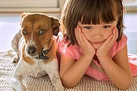 A toddler girl sitting with her sweet puppy pet