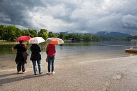 Rear view of three women sheltering under a umbrella. Staffelsee. Upper Bavaria. Germany.