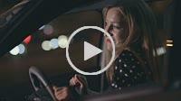 Woman in car having fun at night dancing