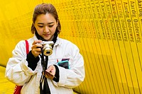 Rotterdam, Netherlands. Young Asian female tourist pondering her just made photographs at Luchtsingel Boardwalk.