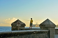 Street photogrphy in central Havana- Malecón (officially Avenida de Maceo) Seawall in the morning with fishermen and distant Morro Castle, La Habana (...