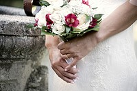 Hands of the bride with bouquet