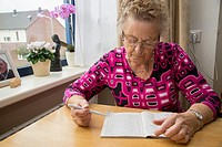 Old woman makes wordpuzzle at table in home for the aged