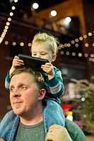 Detroit, Michigan - Two-year-old Adam Hjermstad Jr. looks at a cell phone while riding on the shoulders of his dad, Adam Hjermstad Sr.