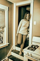 Young woman standing in her kitchen doorway.
