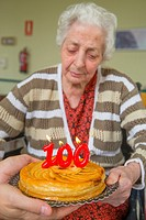 Old woman in a nursing home, on her one hundred birthday, blowing birthday's candles on a cake held by a man's hands.