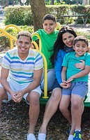 Hispanic family at playground on merry go round portrait smiling Mom and sons Model Released, MR-8, MR-9, MR-10, MR-11.