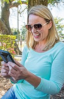 Beautiful blonde woman aged 40s in park texting on phone happy with heart shaped sunglasses modern communicating Model Released, MR-6.
