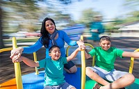 Hispanic family at playground spinning on merry go round speed blurred twist movement Mom and sons Model Released, MR-8, MR-9, MR-11.