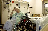 an elderly woman in a wheelchair in a hospital.