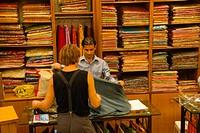 Tourist buying cloth in shop in Delhi, India