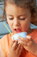 A two years old caucasian girl eating ice cream.