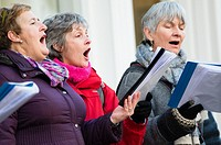 A group of women singing christmas carols on the main street in Aberystwyth collecting to raise money for charity, Wales UK.