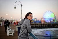 Attractive young woman relaxing in Santa Monica pier, California.