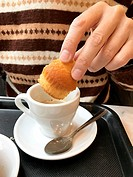 Man dipping a muffin in a cup of coffee, having breakfast.