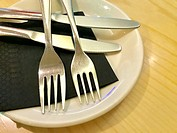 Two forks and two knives on a dish. Close view.
