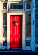 Example of home architecture showing a front red door on a house in Lunenburg, Nova Scotia, Canada.