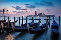 Pre-dawn light over gondolas and San Giorgio Maggiore, Venice, Veneto, Italy.