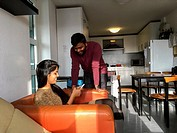 Aachen, Germany. Young, Indian Student´s couple talking in their dormatory kitchen, while diner is cooking.