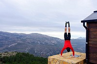 Sportswoman doing handstands in the mountains of Quatretondeta, Alicante, Valencia, Spain
