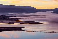 Fog moving over Lake Henshaw during sunrise. San Diego County, California, USA.
