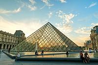 Tourists visiting the famous Louvre Pyramid. Paris. France.