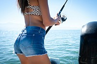 Close up section of female body holding fishing pole - young woman fishing from boat.