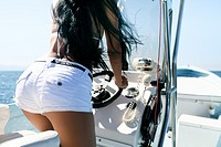 Back side section of dark haired woman driving a motorized fishing boat.