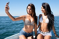 Two very attractive young hispanic women taking a cell phone selfie photo on a boat.
