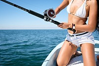 Close up of fishing reel and rod used by attractive young woman on fishing boat.