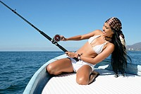 Attractive young hispanic woman leaning back while trying to reel in her catch at fishing off a boat. She looks happy and excited.
